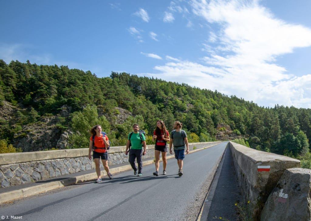 Randonneurs marchant sur un pont avec balise Grande Randonnée